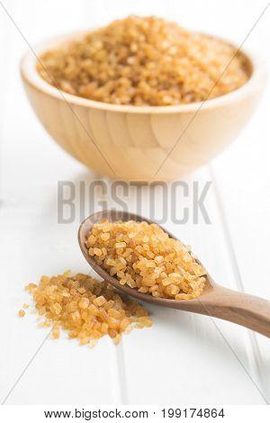 Brown cane sugar in wooden spoon. Crystalline brown sugar.