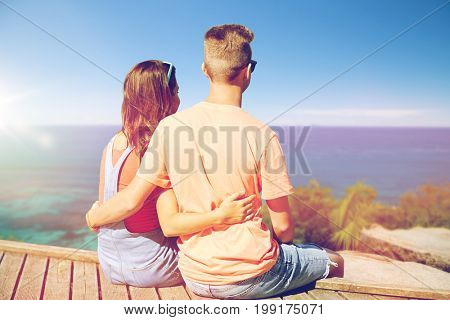 summer holidays, vacation, love and people concept - happy teenage couple sitting on berth over exotic seychelles beach background