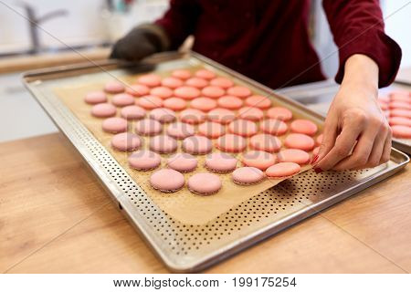 cooking, confectionery and people concept - chef with macarons on oven tray at bakery