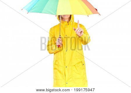 Studio portrait of teenage girl wearing yellow raincoat and holding open colorful umbrella isolated on white