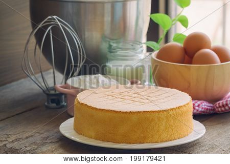 Homemade sponge cake on white plate.Soft and lite delicious sponge cake with ingredients: eggs flour milk on wood table. Homemade cake with ingredients in homemade bakery concept for bakery background. Soft and delicious sponge cake.