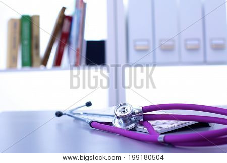 Medical stethoscope lies in the study on the table.