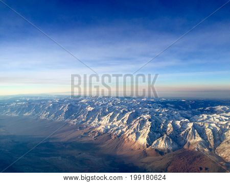Flying over Sierra Mountains in Winter at Sunrise.