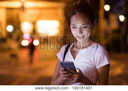 Woman use of mobile phone at night in the city