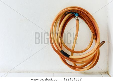 water tap with rolled of old leak rubber tube on white cement wall background, copy space