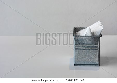 galvanized or zinc tissue box  with folded napkin easy to use on the table, white background, copy space