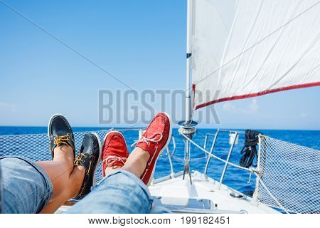Pairs legs of man and woman legs in red and blue topsiders on white yacht deck. Yachting