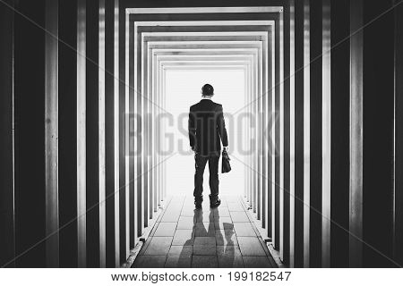 Businessman in line-shaped corridors and confused to exit the unknown bright door .
