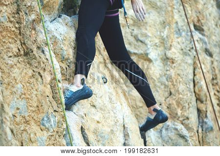 adult woman rock climber. rock climber climbs on a rocky wall. legs and climbing shoes close up