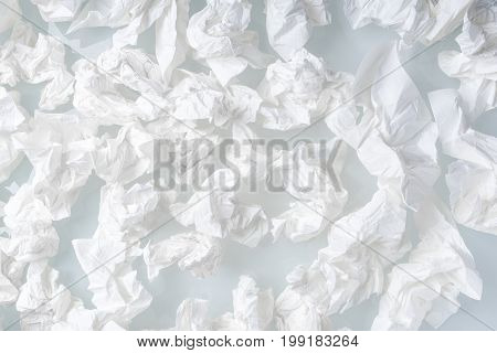 Many used screwed paper tissue on white background - close up