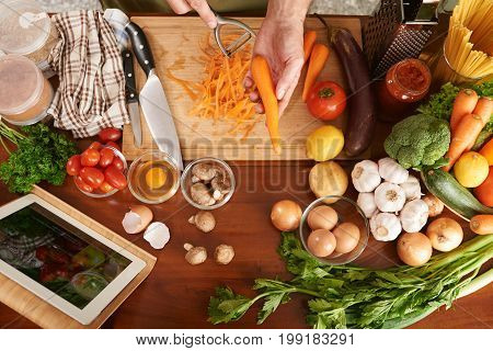 Cook using peeler to make thin stripes of carrot, view from above