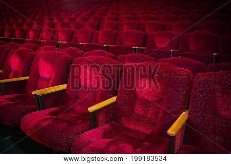 Red velvet armchairs in the empty auditorium. Empty hall