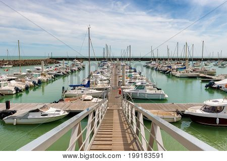 yachts docked in a marina on blue cloudy sky background