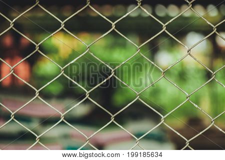 Rusty Chain Link Fence Of Steel Netting On Blur Background.