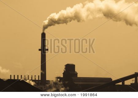 Old-style steel mill smokestack with a sepia filter. poster
