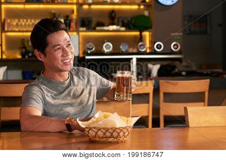 Happy middle-aged Vietnamese man drinking beer and watching match in sports bar