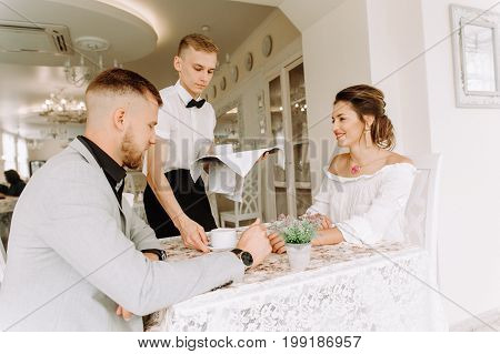 waiter brought cup of coffee for beautiful couple of different people in a cafe, Young Waiter Serving Coffee Couple In Restaurant
