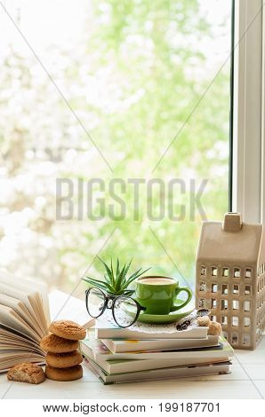 Coffee cup open book glasses cookies and flower on window with bokeh. Reading and breakfast concept. Copy space