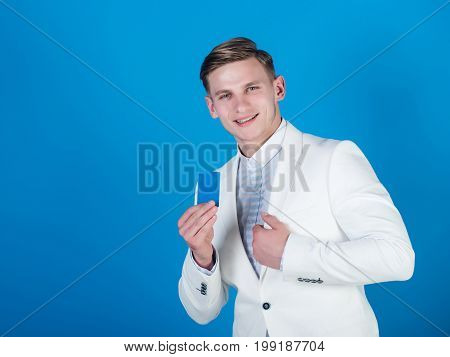 Manager wearing casual suit on blue background. Man smiling with business or bank card. Banking and saving. Businessman posing in white jacket and shirt. Fashion and information concept copy space