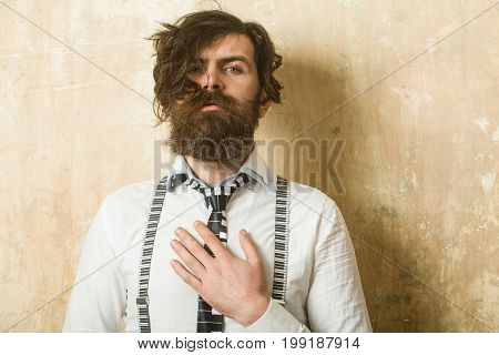 Business fashion and beauty. Guy or businessman at textured wall. Man with long beard and mustache on face. Fashion model with stylish hair. Hipster in shirt and suspenders with musical tie.
