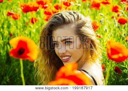 girl. happy smiling woman with long curly hair hold flower in field of red poppy seed with green stem on natural background summer spring drug and love intoxication opium
