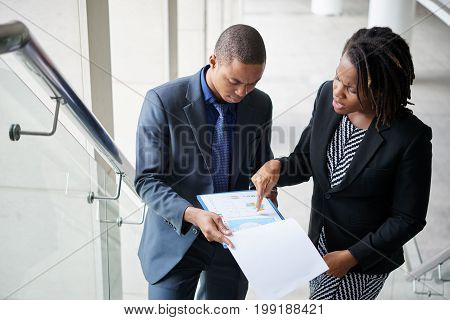 Unhappy business lady showing financial report to male colleague