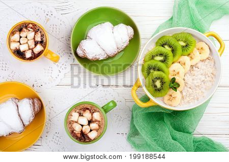 Breakfast with oatmeal porridge croissant fruits and coffee cup. Oatmeal with kiwi and banana. Healthy breakfast and meal concept. Top view