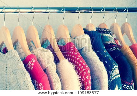 Warm sweaters. Female clothes on open clothes rail. Sale and shopping concept. Toning