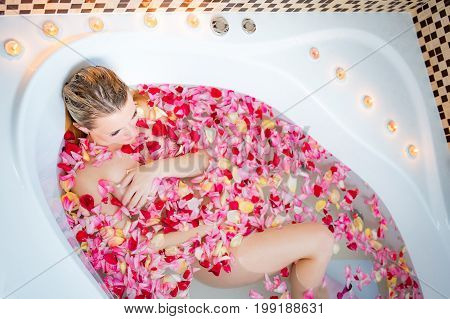 Young beautiful woman relaxing in a bathtub full of rose petals. Spa wellness or body care concept.