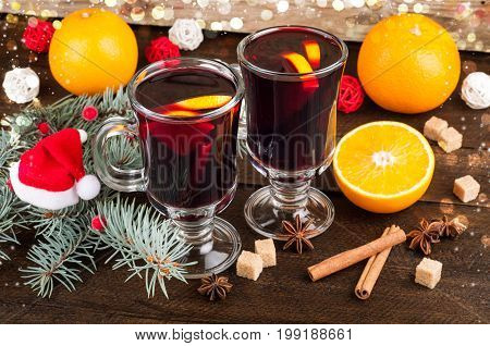 Mulled wine in glass with spices and citrus fruit on bokeh background. Christmas background