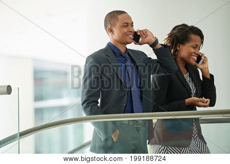 Cheerful business people talking on the phone when going to work