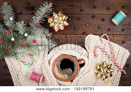 Holidays christmas winter background. Coffee cup and woolen handmade scarf candy canes on wooden table. Copy space