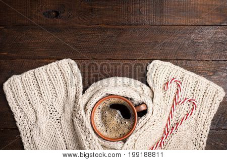 Coffee cup and woolen handmade scarf candy canes on wooden table. Christmas winter background. Copy space