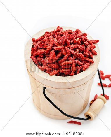 Red dried goji berries wolfberry or lycium chinese herbal medicine in wooden bucket on white background.