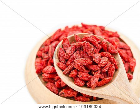 Red dried goji berries wolfberry or lycium chinese herbal medicine in wooden spoon on white background.