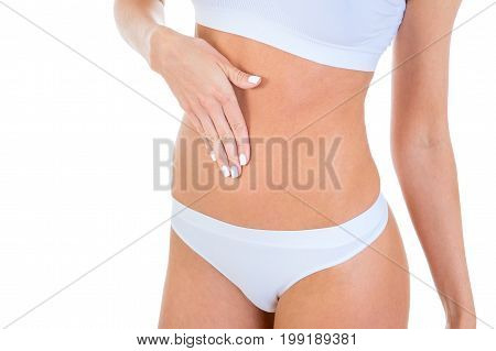 Slim female body in white underwear with hand on her belly on a white background