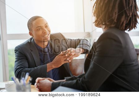 Handsome young businessman conducting interview with female applicant