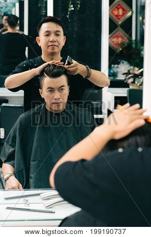 Young Vietnamese man visiting hairdresser to get new haircut