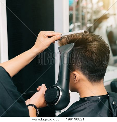 Close-up image of hairdresser blowing out hair of client with fan