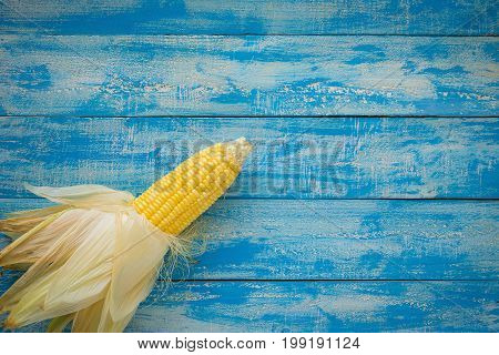 Ripe Corn On A Blue Wooden Table Top View