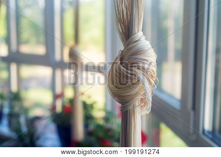 Close up beautiful light beige curtain tied in knot with blurred background
