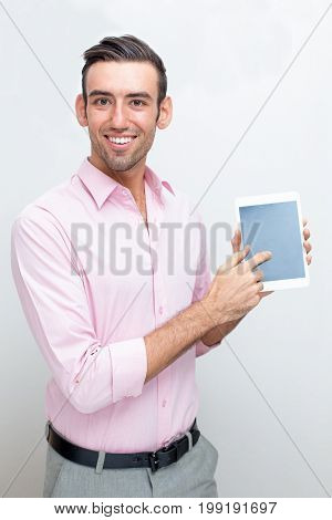 Closeup portrait of smiling young handsome man looking at camera, showing tablet computer screen and pointing at it. Isolated front view on grey background.