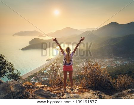 Happy Woman With Raised Up Arms Standing On The Mountain