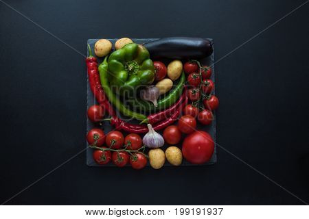 Top View Of Fresh Ripe Tomatoes, Peppers, Garlic, Eggplant And Potatoes On Slate Board