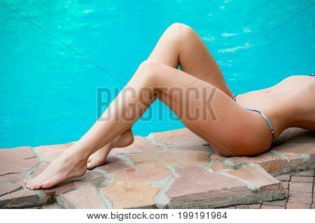 Beautiful slim woman's legs next to the swimming pool