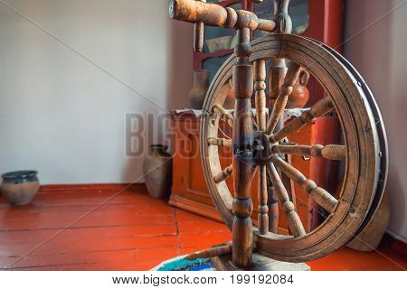 Close up obsolete vintage spinning wheel in room
