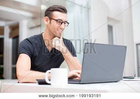 Closeup portrait of smiling young handsome man working on laptop computer at home