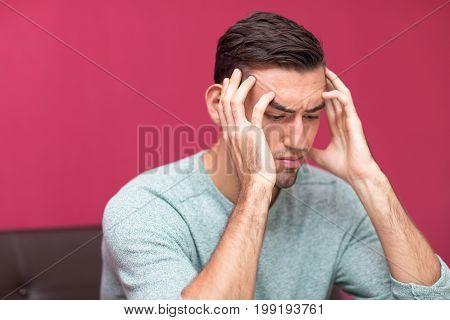 Closeup portrait of tensed young man thinking hard and touching head with fingers at home
