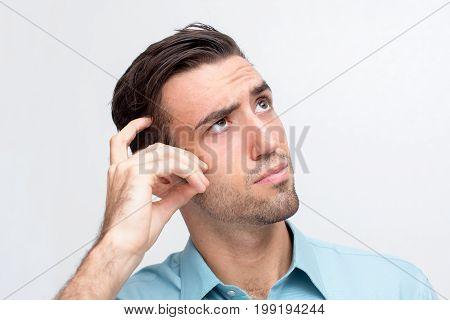 Closeup portrait of thoughtful young handsome man scratching his head and looking upwards. Isolated view on white background.
