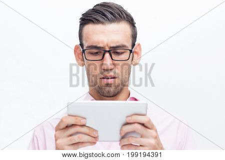 Closeup portrait of worried young handsome man holding tablet computer and looking at its screen. Isolated front view on white background.